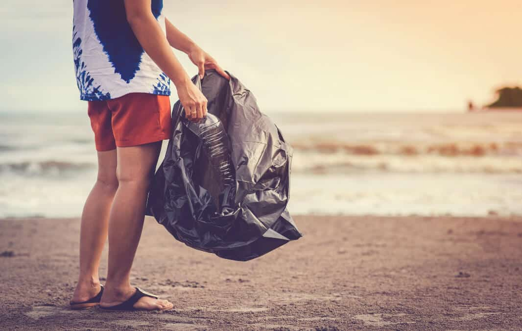 Man holding a black garbage bag at the beach